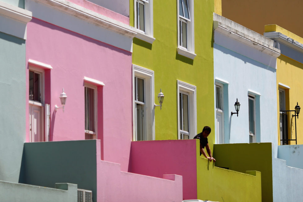CAPE TOWN, SOUTH AFRICA - OCTOBER 20: A man relaxes outside his house in the Bo-Kaap area of Cape Town on October 20, 2009 in Cape Town, South Africa. The Bo-Kaap area is a predominantly Muslim area of Cape Town with brightly coloured painted houses that line many of the streets.. (Photo by Dan Kitwood/Getty Images)