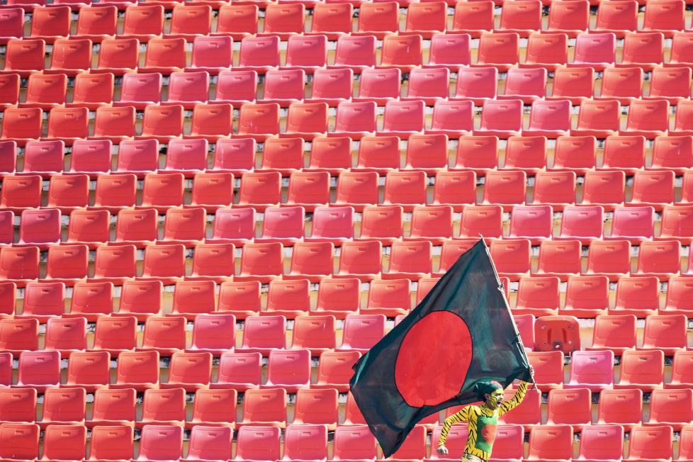 A Bangladeshi cricket fan runs with the national flag to show support for his team during the fourth day's play of the first Test cricket match between Bangladesh and England at Zahur Ahmed Chowdhury Cricket Stadium in Chittagong on October 23, 2016. / AFP PHOTO / Dibyangshu SARKAR