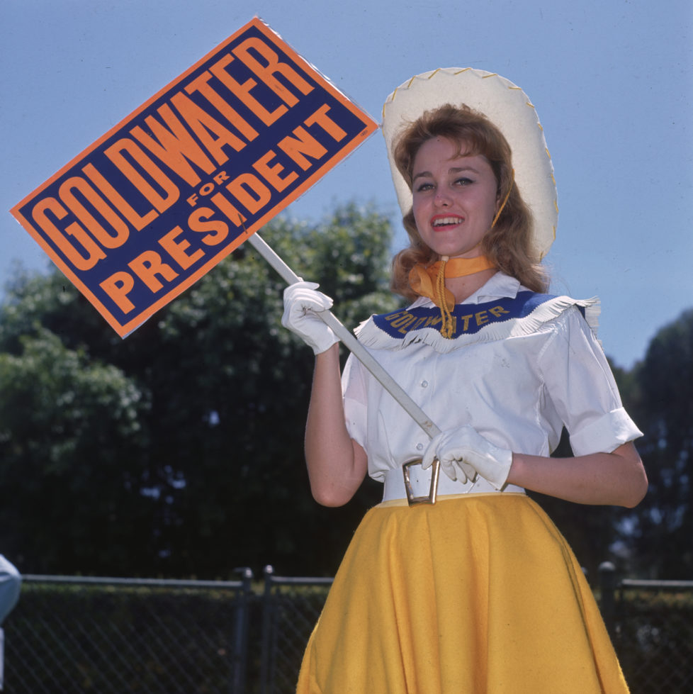 July 1964: A Goldwater girl campaigning for Barry Goldwater, the Republican candidate for the Presidential election, in Sherman Oaks, California. Aged between 18 and 25, the Goldwater Girls will be continuing their support for Goldwater at the Republican Convention in San Francisco. (Photo by Miller/BIPs/Getty Images)