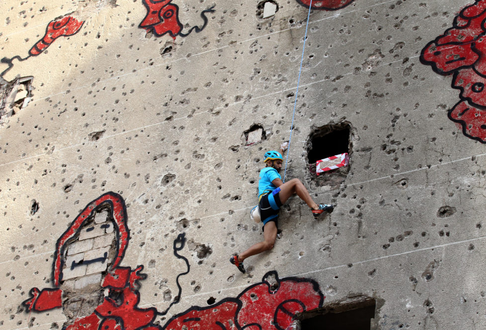 A competitor climbs the hole-ridden facade of Beirut's al-Kamal building, which was severely damaged during the Lebanese civil war (1975-1990), during an urban climbing contest on November 12, 2016. The contestants will compete in three rounds in order to select the winner who has achieved the fastest possible time to reaching the top. / AFP PHOTO / ANWAR AMRO
