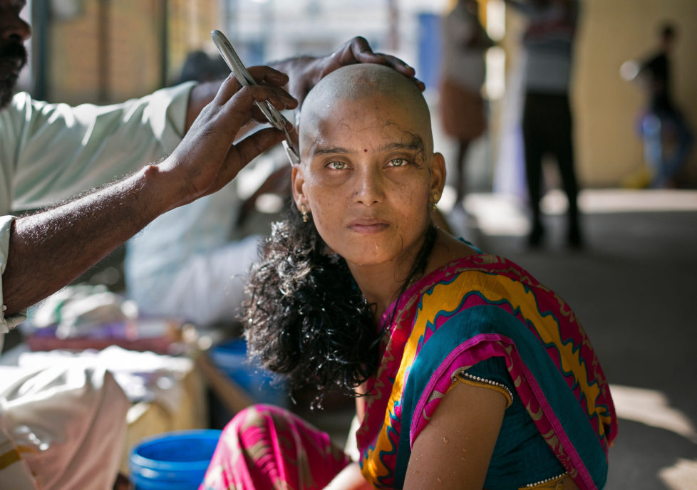 "THIRUTTANI, INDIA - NOVEMBER 10: 28 year old Rupa has her hair shaven to donate to the Gods at the Thiruthani Murugan Temple November 10, 2016 in Thiruttani, India. Rupa donated her hair with the wish that her daughter's illness is cured. The process of shaving ones hair and donating it to the Gods is known as tonsuring. It is common for Hindu believers to tonsure their hair at a temple as a young child, and also to celebrate a wish coming true, such as the birth of a baby or the curing of an illness. The ""temple hair"", as it's known, is then auctioned off to a processing plant and then sold as pricey wigs and weaves in the US, Europe and Africa. (Photo by Allison Joyce/Getty Images)"