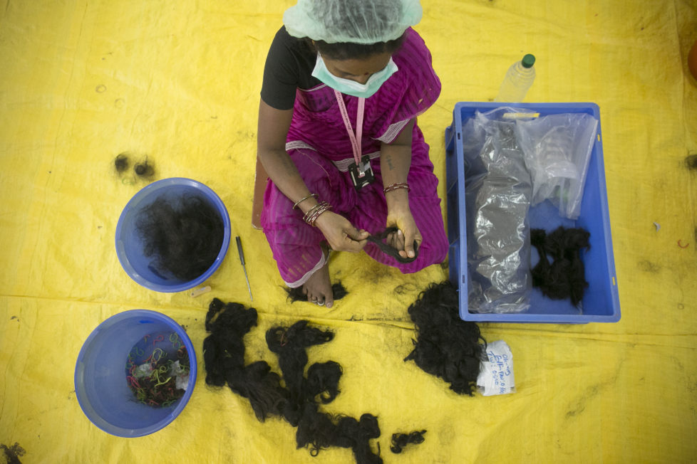 "CHENNAI, INDIA - NOVEMBER 11: A worker processes hair at Raj Hair International November 11, 2016 in Thiruttani, India. Raj Hair International donates wigs to cancer patients in India and also exports hair products, including weaves and wigs, to 56 countries. All of the hair they export comes from Tamil Nadu, 1/4 of which is temple hair and the rest comes from comb waste that people sell. They estimate that it takes 1 full month to make one wig by hand. The process of shaving ones hair and donating it to the Gods is known as tonsuring. It is common for Hindu believers to tonsure their hair at a temple as a young child, and also to celebrate a wish coming true, such as the birth of a baby or the curing of an illness. The ""temple hair"", as it's known, is then auctioned off to a processing plant and then sold as pricey wigs and weaves in the US, Europe and Africa. (Photo by Allison Joyce/Getty Images)"