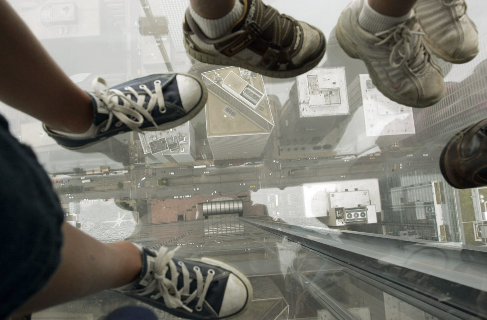 """Children stand on """"The Ledge"""" and look down through a glass floor 1,353 feet (412 meters) above Wacker Drive in Chicago July 1, 2009. The Ledge is part of Skydeck Chicago located on the 103rd floor of the Sears Tower. It opens to the public on July 2. REUTERS/Frank Polich (UNITED STATES SOCIETY IMAGES OF THE DAY) - RTR258BY"""
