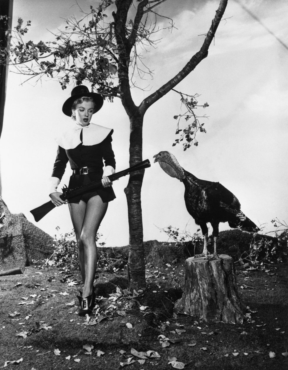 "(Original Caption) 11/10/1950-Hollywood, California- Wearing a costume that is half-Puritan, half-chorine, pretty Marilyn Monroe seems to have little desire to hunt turkey after finding this gobbler, still ""stumping"" long after Election Day. Currently seen in ""All About Eve,"" this movie starlet seems just as frightened by the gun as the bird is."