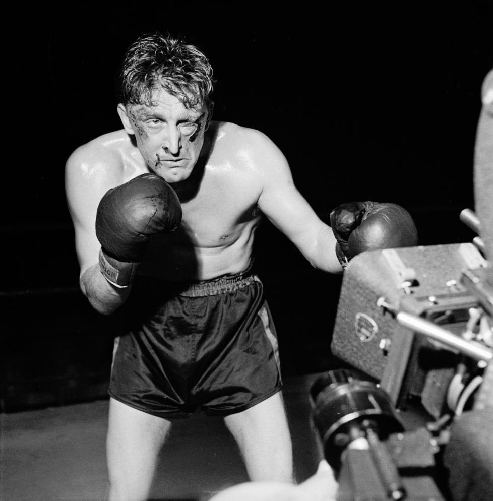 American actor Kirk Douglas poses in front of a movie camera for a publicity still to promote his film 'Champion,' directed by Mark Robson, 1949. Douglas wears boxing gloves and shorts, and sports makeup simulating a swollen left eye and bloody cuts. (Photo by Peter Stackpole/The LIFE Picture Collection/Getty Images)