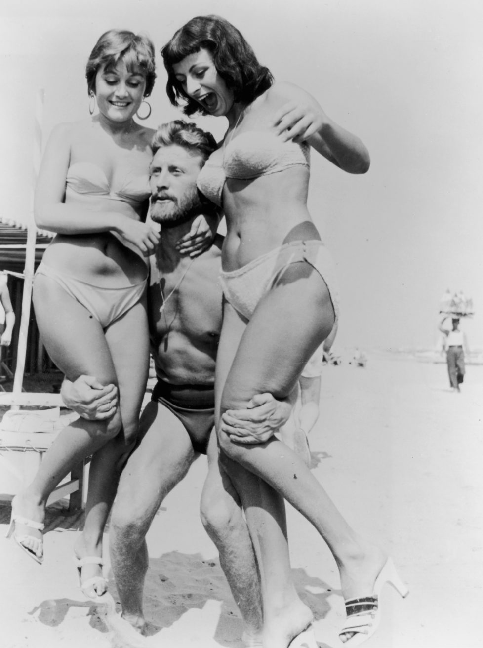 1953: American actor Kirk Douglas, wearing a swimsuit, lifts two women wearing bikinis on a beach during the Venice Film Festival, Italy. (Photo by Hulton Archive/Getty Images)