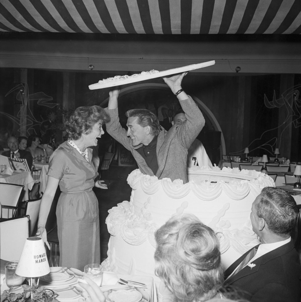 "(Original Caption) 4/24/1959-Palm Springs, California- Shrieking with delight, Anne Douglas does a double-take as her actor husband Kirk Douglas pops up out of a giant birthday cake. Douglas, wearing his hair long for his role in ""Spartacus,"" came secretly from Hollywood and hid out in the cake to surprise his wife at her birthday party at the Howard Manor."