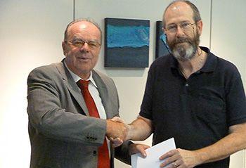 Herr Rrr (links) gratuliert Herrn Lattenknaller und übergibt ihm den Gutschein für 11 YB-Würste.